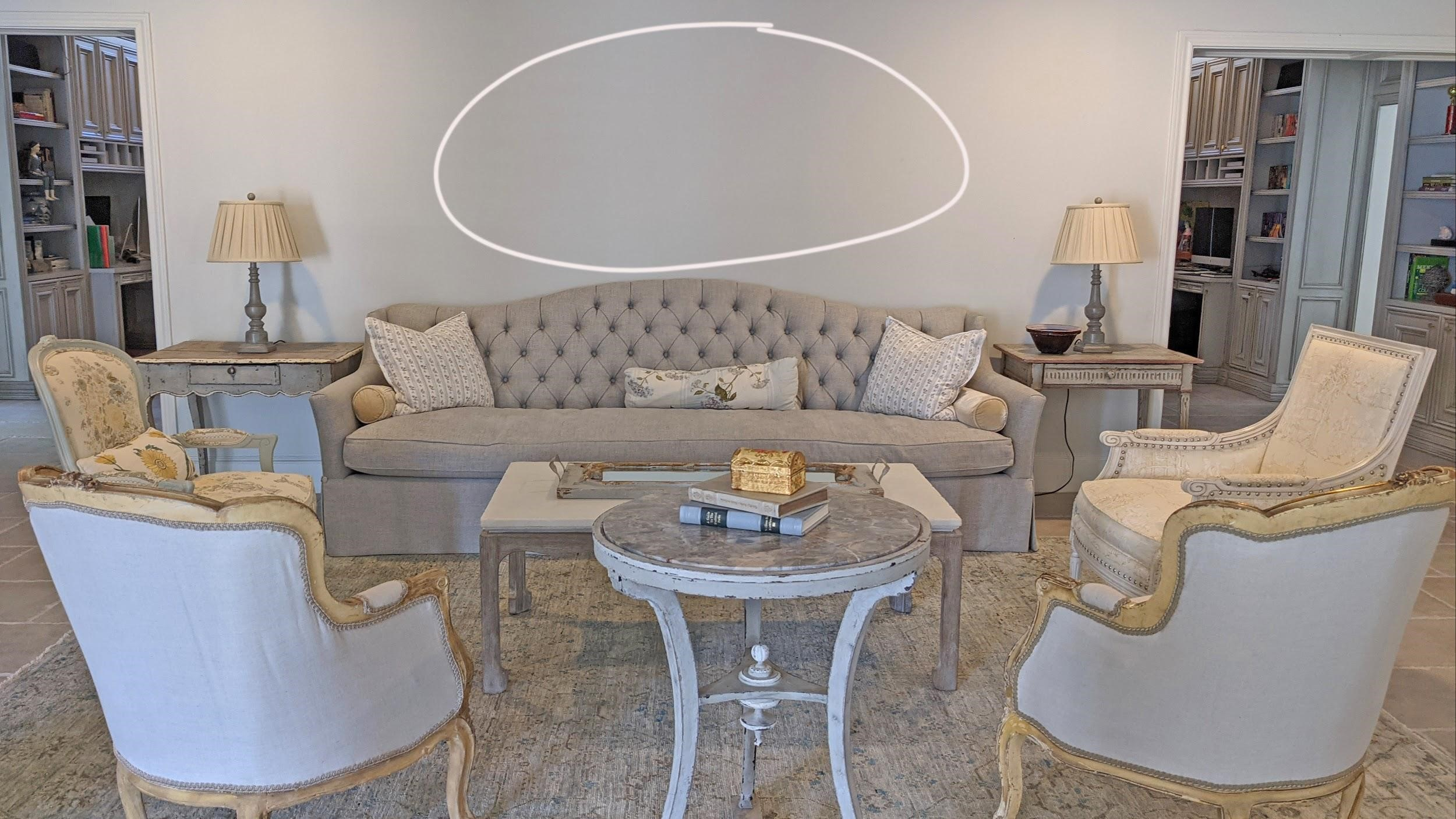 Amitha's living room with long gray French country sofa needs artwork on the wall