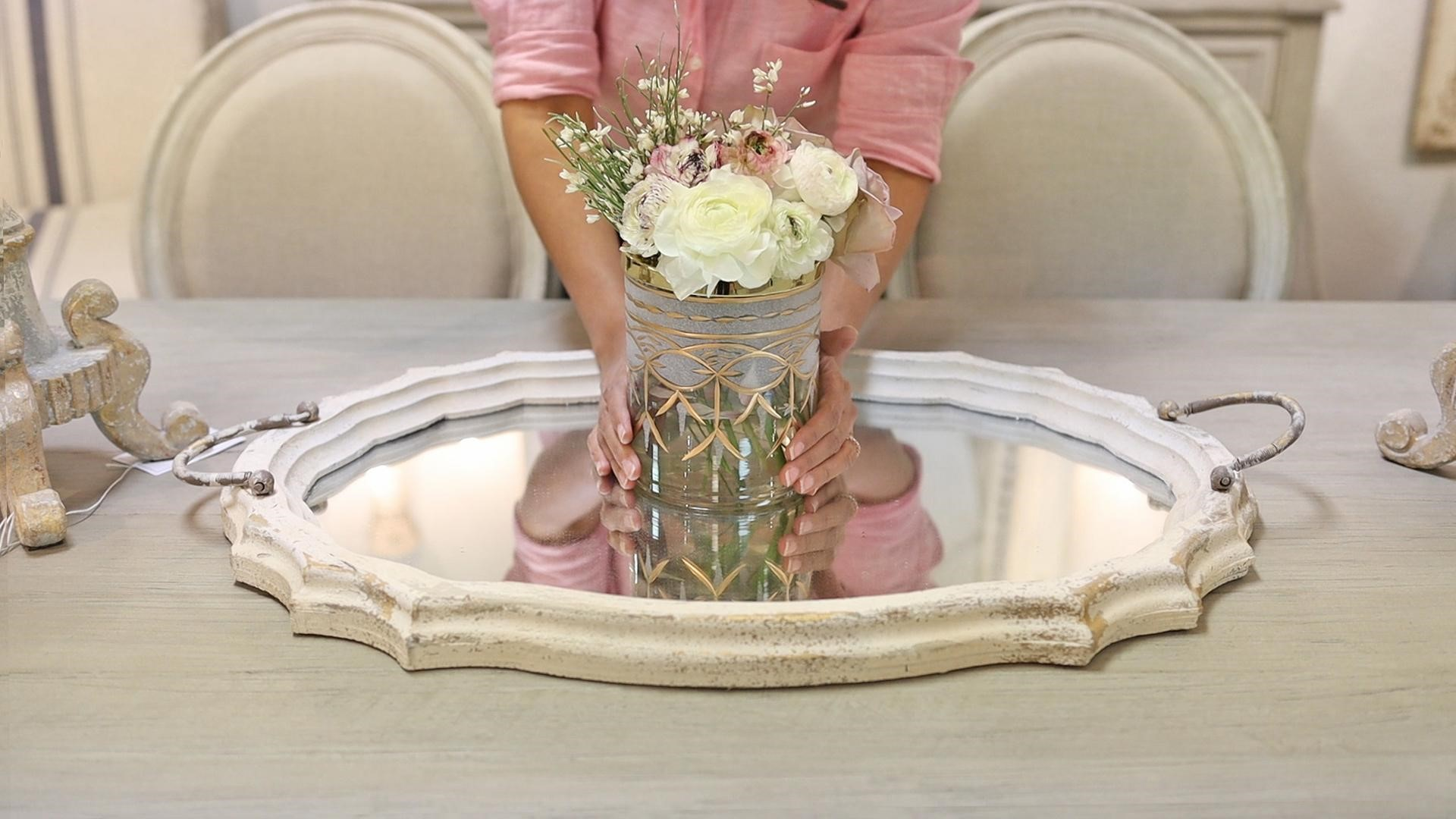 Amitha places medium floral arrangement in a short cylindrical vase on a mirrored tray